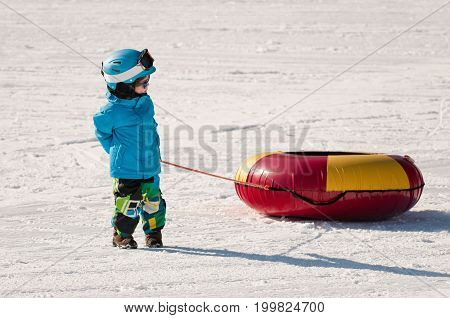 Little Boy Preparing For Snow Tubing, White Background. Color Image.