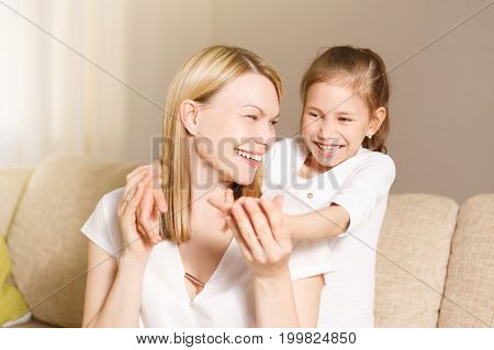 Young Girl Is Closing Her Mother Eyes. Beautiful Mother And Her Little Daughter Are Smiling. People