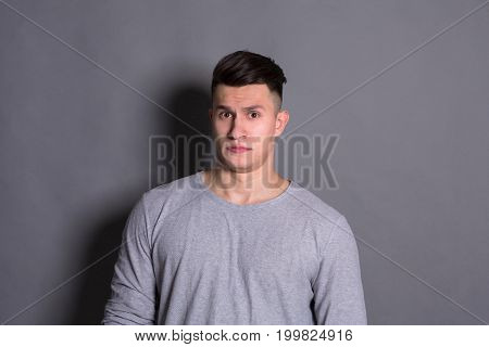 Negative human emotion. Man expressing annoyance on face, grimacing on grey studio background