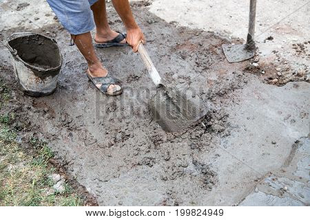 Worker mixes concrete with a shovel at the construction site