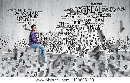 Young man in casual wear sitting among flying letters with business-related terms in form of world map on background. Mixed media.