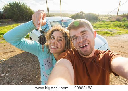 Portrait of happy beautiful laughing cheerful couple showing the keys standing near the car. Customer, car sale, deal and people concept.