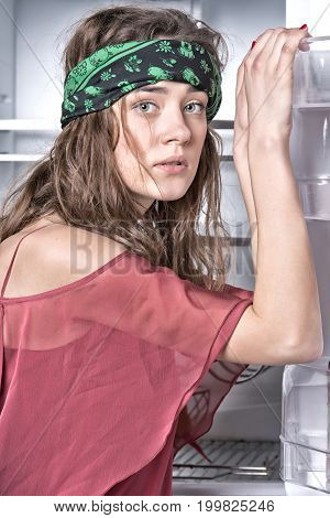 Woman Posing At Open Fridge Door With Empty Shelves