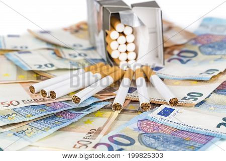 20 and 50 Euro banknotes bills cash with cigarettes with cigarettes box. Concept of cost of tabacco cigarettes. Front and top view close-up.