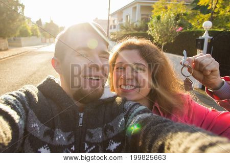 Funny couple With Keys Standing Outside New Home. Real estate, owner and people concept.
