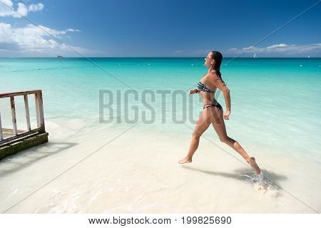 Girl with sexy body in bikini running on beach with white sand turquoise sea and blue sky on sunny day on natural environment. Sun tanning bathing. Summer vacation. Rest relaxing active leisure
