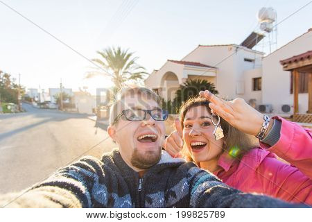 happy young laughing cheerful couple man and woman handing their new home keys in front of a house.