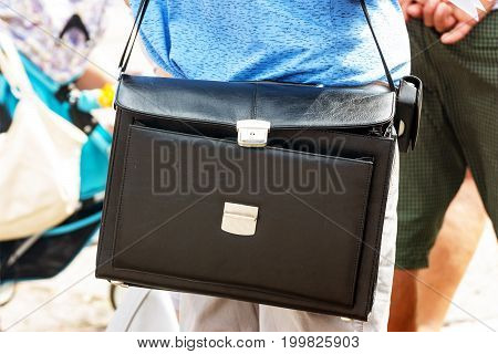Open black briefcase of leather on the shoulder of a man
