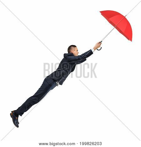 A businessman holds to an open red umbrella that keeps him afloat in the air. Safety and protection. Insurance policy. Dream business.