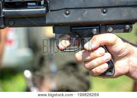 Finger on the trigger of an army machine gun