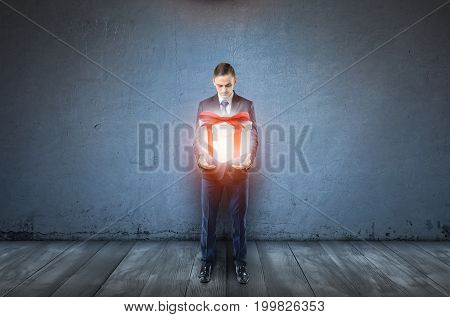A businessman on dark blue background holds a large glowing giftbox. Good fortune. Bonuses and promotions. Gift of fate.