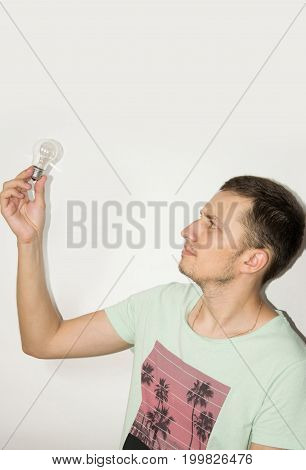 Casual man holding a lightbulb isolated on grey background