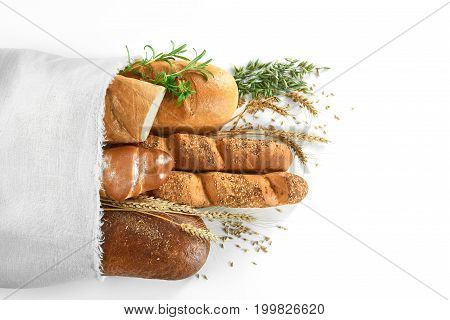 Top view shot of a paper bag with different kinds of delicious freshly baked  bread loafs copyspace isolated on white.