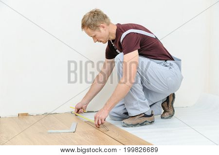 Installation of a laminate floorboard. The worker is measuring the distance to the wall.