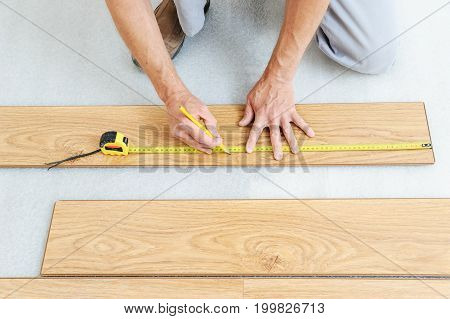 Installation of a laminate floorboard. Worker's hands are measuring a piece of board to cut into the future.