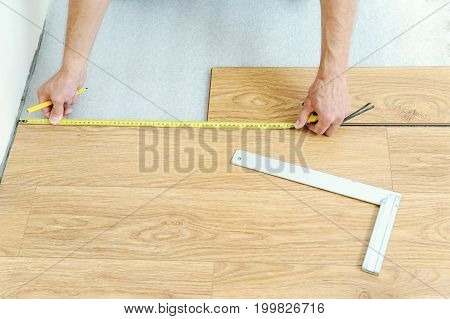 Installation of a laminate floorboard. Worker's hands are measuring the distance to the wall.