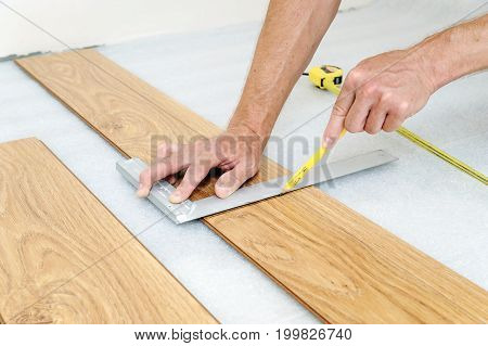 Installation of a laminate floorboard. Worker's hands are marking the cutting line.