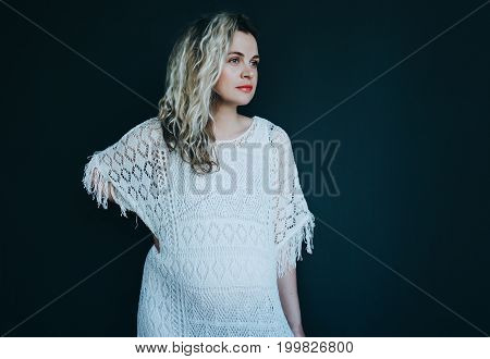 Pregnant curly-haired woman in a white dress on a dark background. Place for your text.