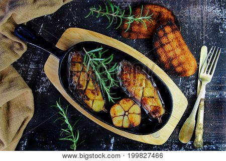 eggplant grilled in a cast iron skillet with rosemary