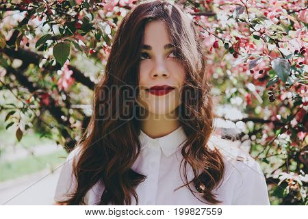 Romantic beautiful girl with red lips in blooming trees in the park.