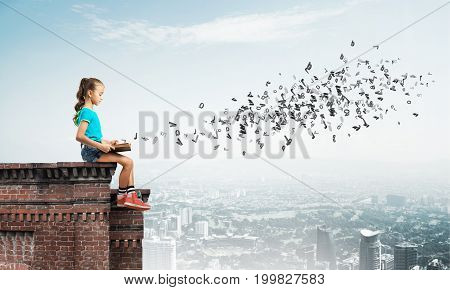 Cute kid girl sitting on building roof reading book and letters fly in air
