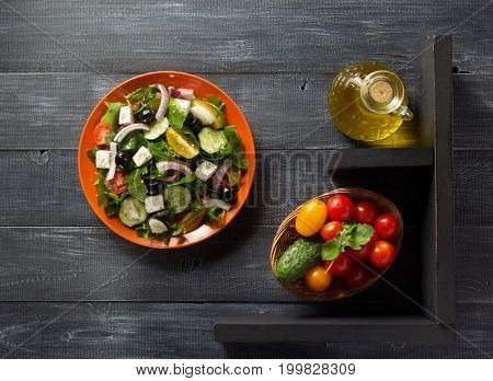 fresh greek salad in plate and ingredients on wooden table