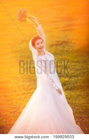 Side view portrait of happy bride holding flower bouquet on grassy field