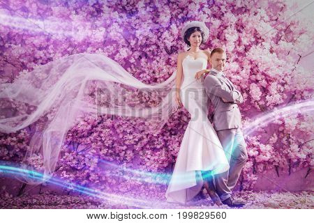 Portrait of confident wedding couple standing against wall covered with pink flowers