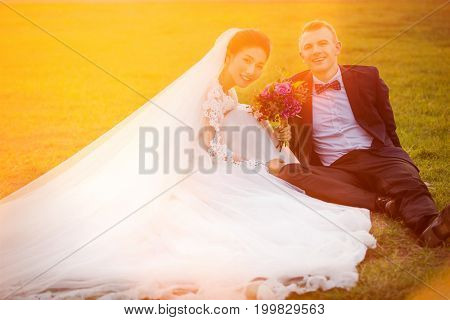 Portrait of smiling wedding couple sitting on grassy field