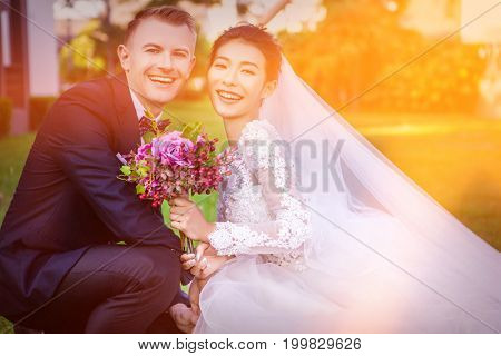 Portrait of happy wedding couple crouching at lawn