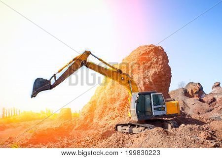 A large construction excavator of yellow color on the construction site in a quarry for quarrying