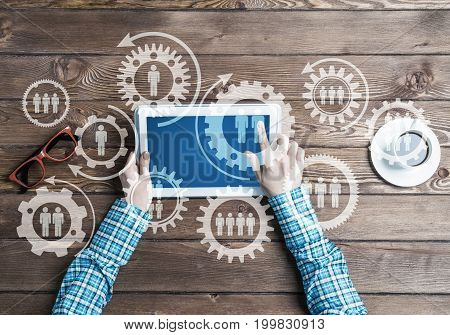 Top view of woman in checked shirt sitting at table and using tablet device