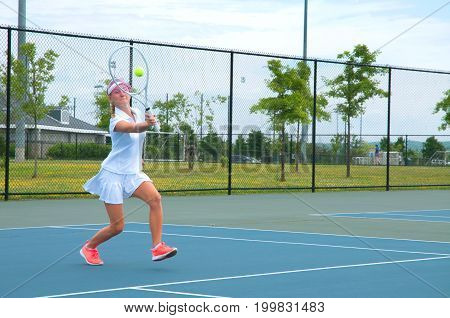 Young Woman Is Playing Tennis On The Tennis Court