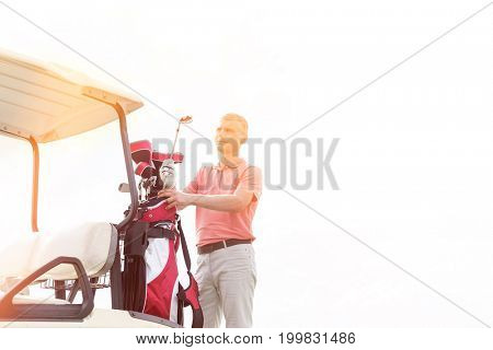 Thoughtful middle-aged man standing by cart against clear sky
