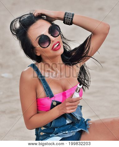 Young Sexy Woman With Big Breast Vaping E-cigarette Sitting On The Beach