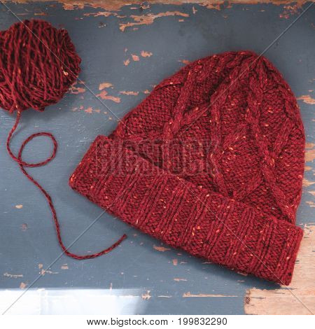 Red knitted tweed hat with a pattern on a gray background