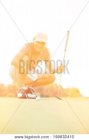 Smiling middle-aged man looking at ball while crouching on golf course