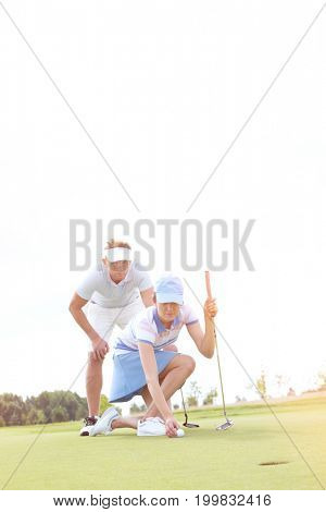 Man looking at woman aiming ball on golf course against sky