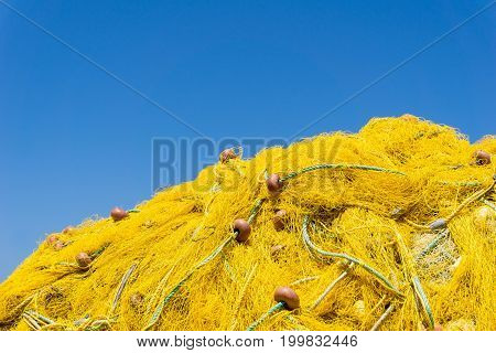 Close-up of yellow Fishing Nets in front of a blue Sky. View on stacked Fishing Nets. Fishing Industry. Natural Background.