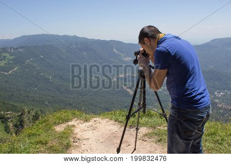 Traveller looking the nature from the high mountain with spotting scope binoculars tripod. Eco tourism and healthy lifestyle concept