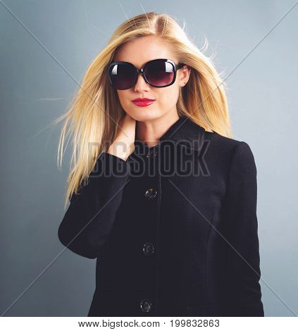 Beautiful young blonde woman in a black coat and sanglasses