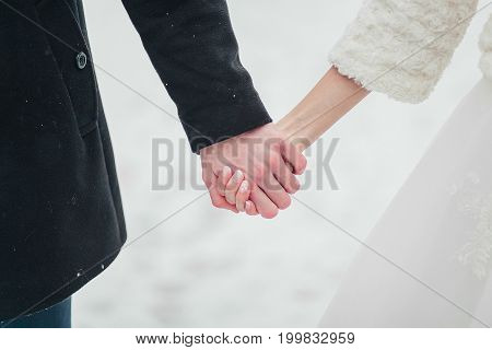 The Bride And Groom Hand In Hand In Winter