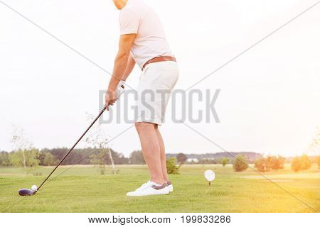 Low section side view of man playing golf against clear sky