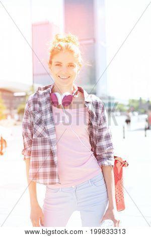 Portrait of happy woman standing on city street