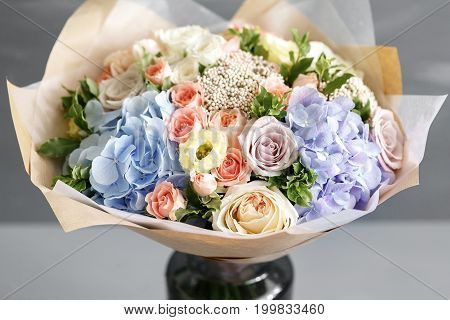 beautiful bouquet made of different flowers on grey background. colorful color mix flower. gray wall