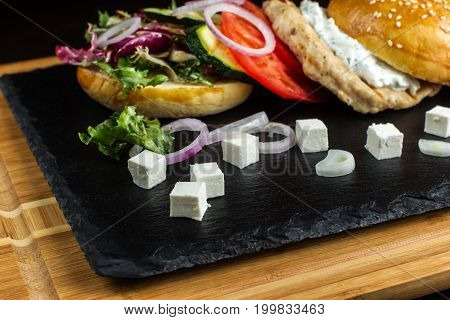 Open hamburger lies on the slate tile. In the foreground is cheese cut into cubes, side view.