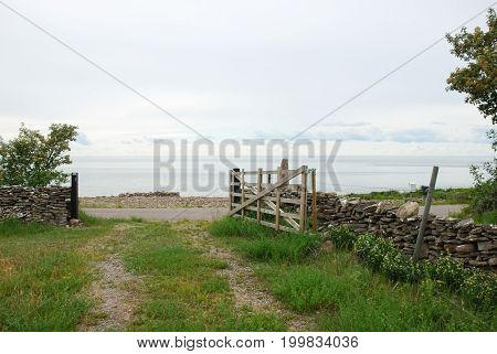Old fashioned wooden gate by a pathway to the sea at the swedish island Oland