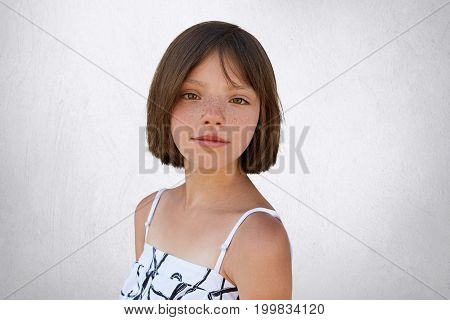 Good-looking Brunette Kid With Freckles And Short Hair Posing Against White Concrete Wall Dressed In