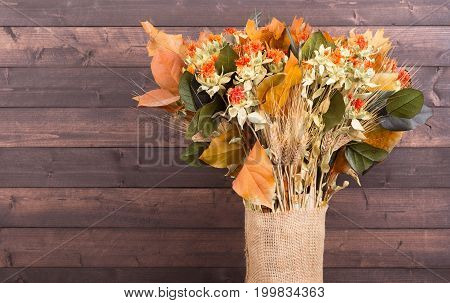 Colorful autumn dried flower bouquet on a rustic wood background
