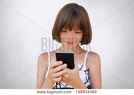 Pretty Little Girl Looking Attentively Into Her Smart Phone While Watching Cartoons Online Using Fre